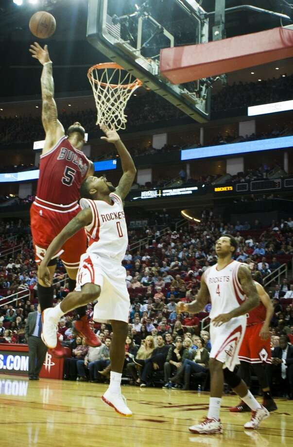 Bulls power forward Carlos Boozer (5) blocks a shot by Rockets point guard Aaron Brooks (0). Photo: Marie D. De Jesus, Houston Chronicle