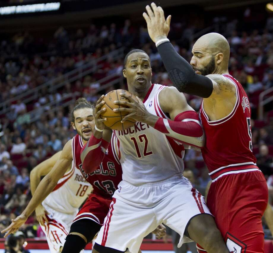 Rockets power forward Dwight Howard, center, (12) looks a way to make a pass under the pressure of Bulls power forward Carlos Boozer, right, (5) and Joakim Noah (13). Photo: Marie D. De Jesus, Houston Chronicle