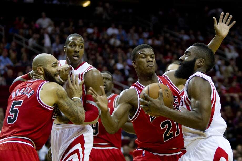 Rockets shooting guard James Harden (13) moves toward the basket under the pressure of Bulls shooting guard Jimmy Butler (21). Photo: Marie D. De Jesus, Houston Chronicle