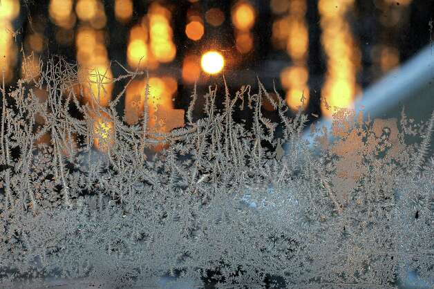 The morning sun is seen rising through trees beyond a frosty window on Thursday, Dec. 19, 2013 in Guilderland, N.Y. (Lori Van Buren / Times Union) Photo: Lori Van Buren