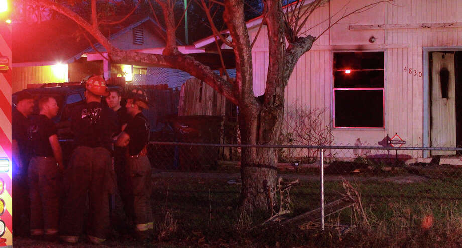 San Antonio firefighters congregate Thursday December 19, 2013 in front of a home on the 4800 block of Castle Pine where a fire broke out about 5:00 a.m. . Fire Captain Michael Moore said smoke was seen upon arrival and two victims in the home were transported to San Antonio Military Medical Center in undetermined condition. Moore said the fire started in the front living room and arson investigating the cause of the fire. Photo: JOHN DAVENPORT, SAN ANTONIO EXPRESS-NEWS / ©San Antonio Express-News/Photo may be sold to the public