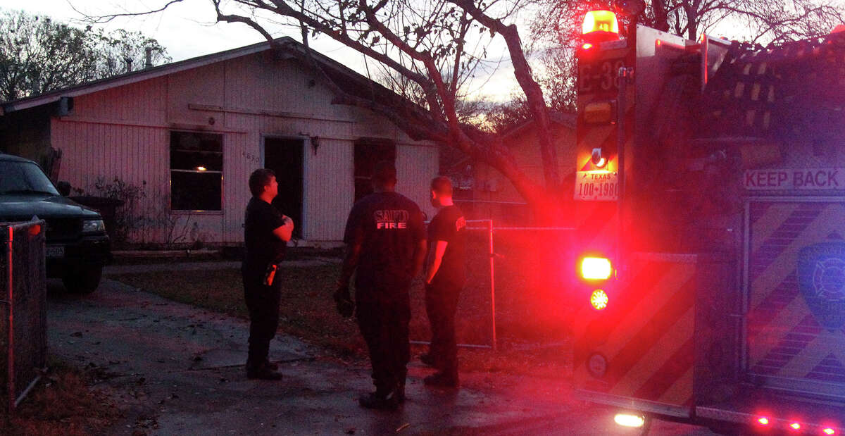 San Antonio firefighters congregate Thursday December 19, 2013 in front of a home on the 4800 block of Castle Pine where a fire broke out about 5:00 a.m. . Fire Captain Michael Moore said smoke was seen upon arrival and two victims in the home were transported to San Antonio Military Medical Center in undetermined condition. Moore said the fire started in the front living room and arson investigating the cause of the fire.