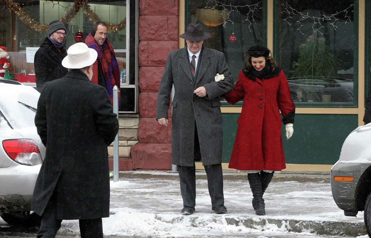 """Actors dressed in period costume from the movie """"It's A Wonderful Life"""" roamed the streets of Seneca Falls, N.Y., Saturday, Dec. 14, 2013. The village of Seneca Falls is transformed into Bedford Falls every year for the annual weekend festival honoring the classic. The village is thought to be the inspiration for the movie. (AP Photo/Finger Lake Times, Spencer Tulis) ORG XMIT: NYGEN106"""