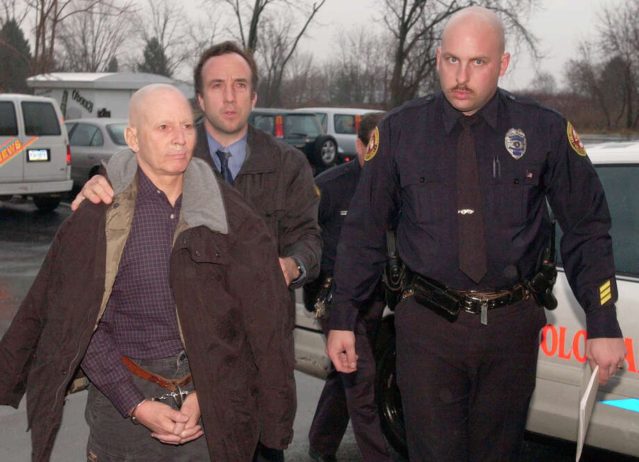 Fugitive Robert Durst, in handcuffs, is escorted to his arraignment in Bethlehem, Pa., Friday, Nov. 30, 2001, by Colonial Regional officers Gary Hammer, left, and  Dean Benner, right.  Durst, the estranged scion of one of New York's wealthiest real estate families wanted on a murder charge, was arrested while stealing a sandwich, police said. (AP Photo/The Morning Call, Pete Shaheen).     HOUCHRON CAPTION (12/01/2001):   Fugitive Galveston murder suspect Robert Durst, left, is escorted to his arraignment by Bethlehem, Pa., officers Gary Hammer, left, and Dean Benner. Photo: PETE SHAHEEN, AP / THE MORNING CALL