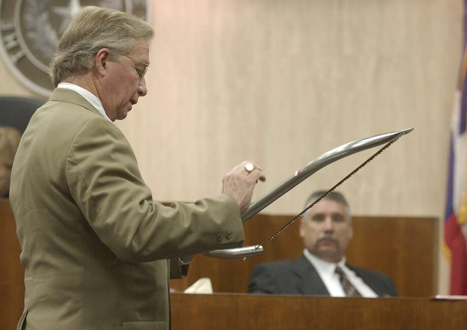 Lead defense attorney Dick DeGuerin, left, shows a bow saw to Galveston Police Sgt. Cody Cazalas, right, during cross examination during the trial of multi-millionaire murder suspect Robert Durst Monday, Oct. 20, 2003, in Galveston Photo: PAT SULLIVAN, AP / AP
