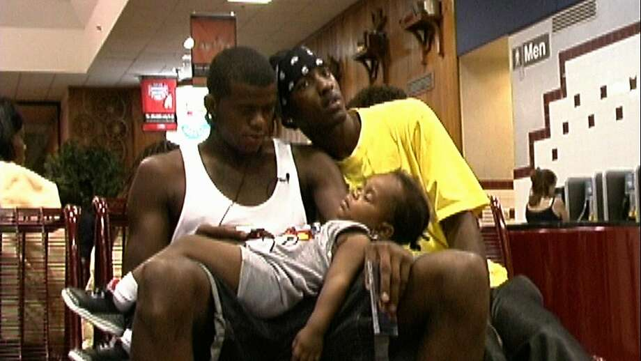Lenny Cooke (left) cradles his son, Anahijae, while sitting with his friend Damany Eastman. Photo: Josh Heller
