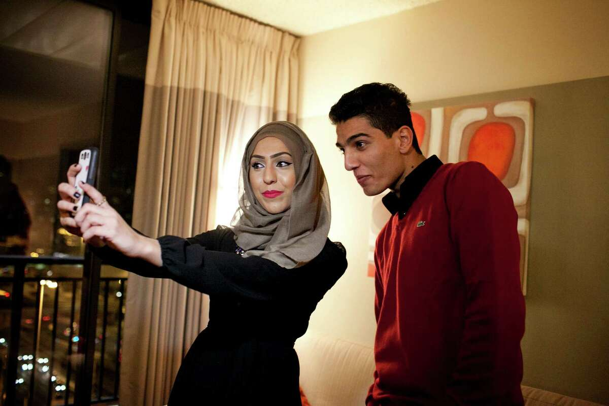 """Mohammed Assaf poses for a photograph in Chicago with fan Marwa Abed. Assaf, a Middle Eastern star since winning """"Arab Idol"""" in June, has played to packed houses on a nine-week tour of North America."""