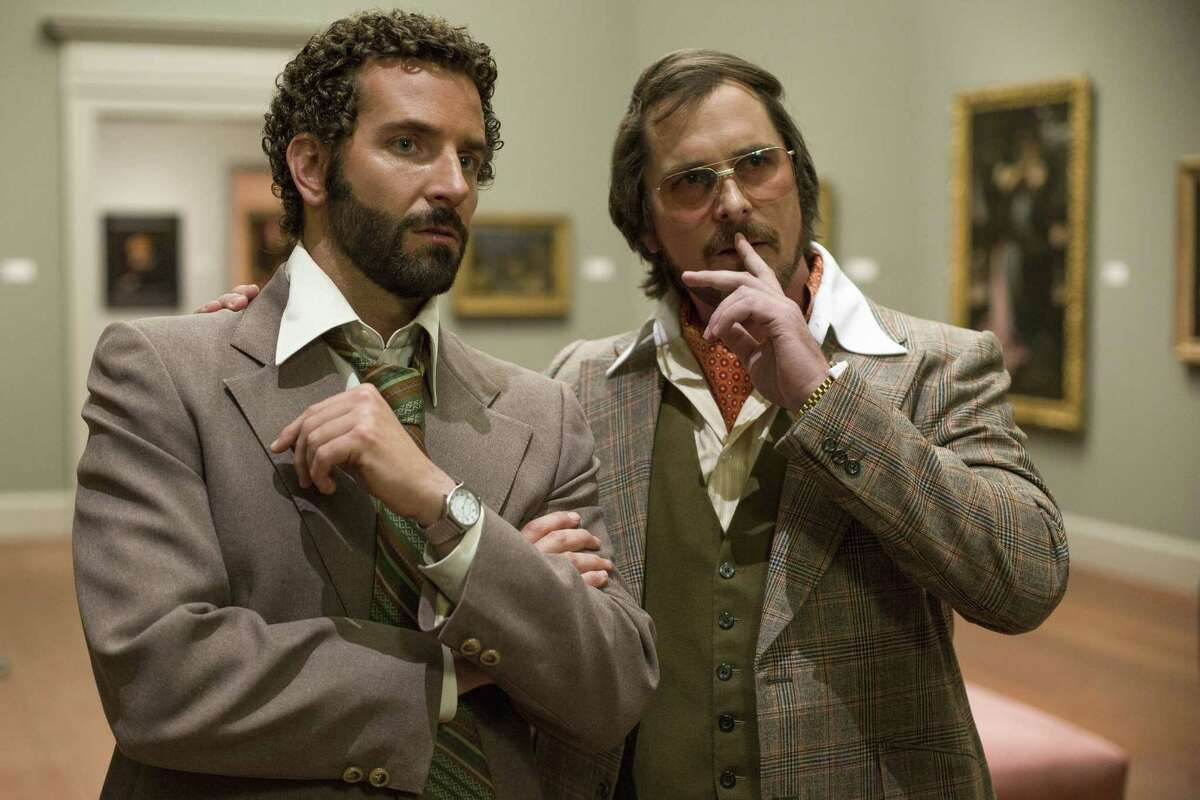 """Bradley Cooper, left, and Christian Bale star as an FBI agent and a con man in """"American Hustle."""""""
