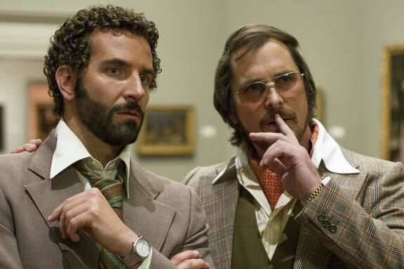 "Bradley Cooper, left, and Christian Bale star as an FBI agent and a con man in ""American Hustle."""