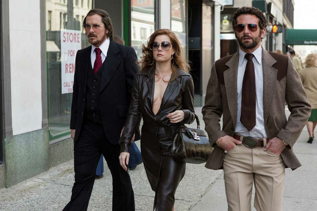 """This photo released by Sony Pictures shows Christian Bale, left, as Irving Rosenfeld, Amy Adams as Sydney Prosser, and Bradley Cooper as Richie Dimaso walking down Lexington Avenue in a scene from Columbia Pictures' film, """"American Hustle."""" (AP Photo/Sony - Columbia Pictures, Frané§ois Duhamel)"""