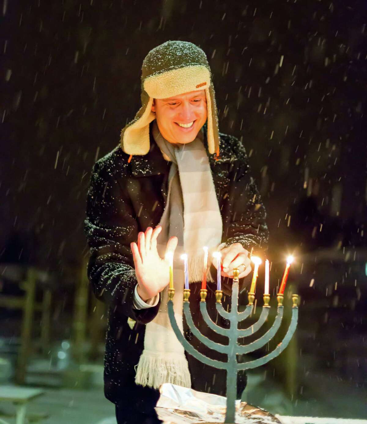 Josh Zapin lights a menorah in the snow with the Adventure Rabbi program in Boulder, Colo.