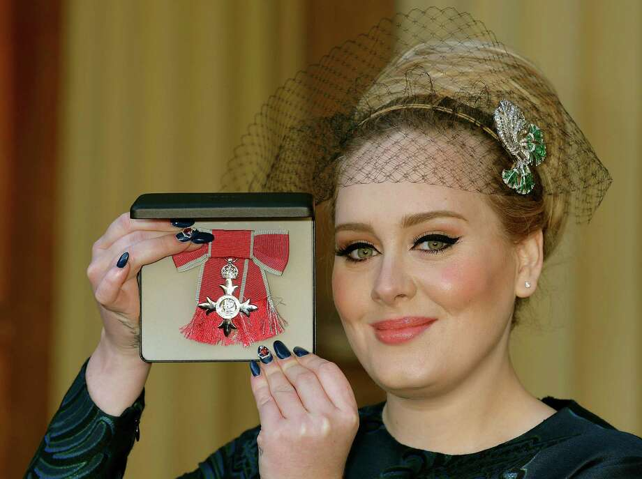 British singer Adele Adkins holds her MBE for services to music presented to her by the Prince of Wales at Buckingham Palace in London, Thursday, Dec. 19, 2013. (AP Photo/John Stillwell, Pool) ORG XMIT: LON114 Photo: John Stillwell / Pool PA