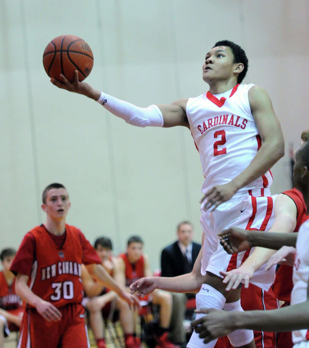 At right, C.J. Byrd (# 2) of Greenwich goes in for a lay-up getting past New Canaan's Paul Hagopian (# 30), left, during the boys varsity basketball game between Greenwich High School and New Canaan High School at Greenwich, Wednesday night, Dec. 18, 2013.