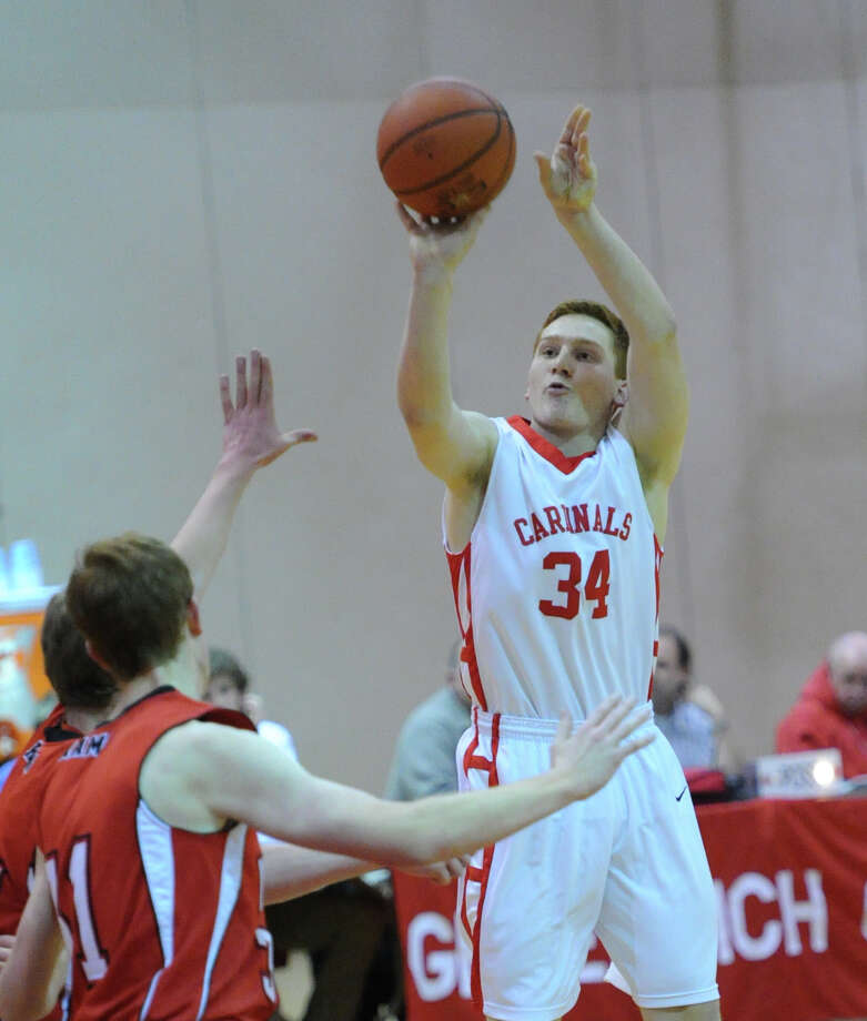At right, Griffin Golden (# 34) of Greenwich shoots during the boys varsity basketball game between Greenwich High School and New Canaan High School at Greenwich, Wednesday night, Dec. 18, 2013. Photo: Bob Luckey / Greenwich Time