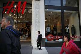 "Pedestrians walk past a H & M store on Powell street displaying an ""Up to 60% Off"" sign on the front window on Thursday, December 19, 2013  in San Francisco, Calif."