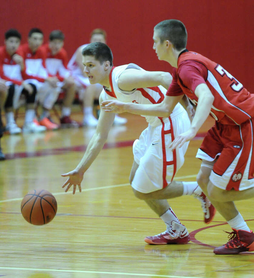At left, Tom Povinelli (# 3) of Greenwich drives around a New Canaan defender during the boys varsity basketball game between Greenwich High School and New Canaan High School at Greenwich, Wednesday night, Dec. 18, 2013. Photo: Bob Luckey / Greenwich Time