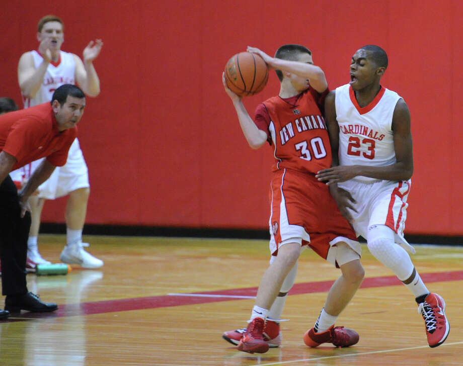 At left, Greenwich basketball coach Bill Brehm looks on as his player, Leonel Hyatt (# 23), right, defends against New Canaan's Paul Hagopian (# 30) during the boys varsity basketball game between Greenwich High School and New Canaan High School at Greenwich, Wednesday night, Dec. 18, 2013. Photo: Bob Luckey / Greenwich Time