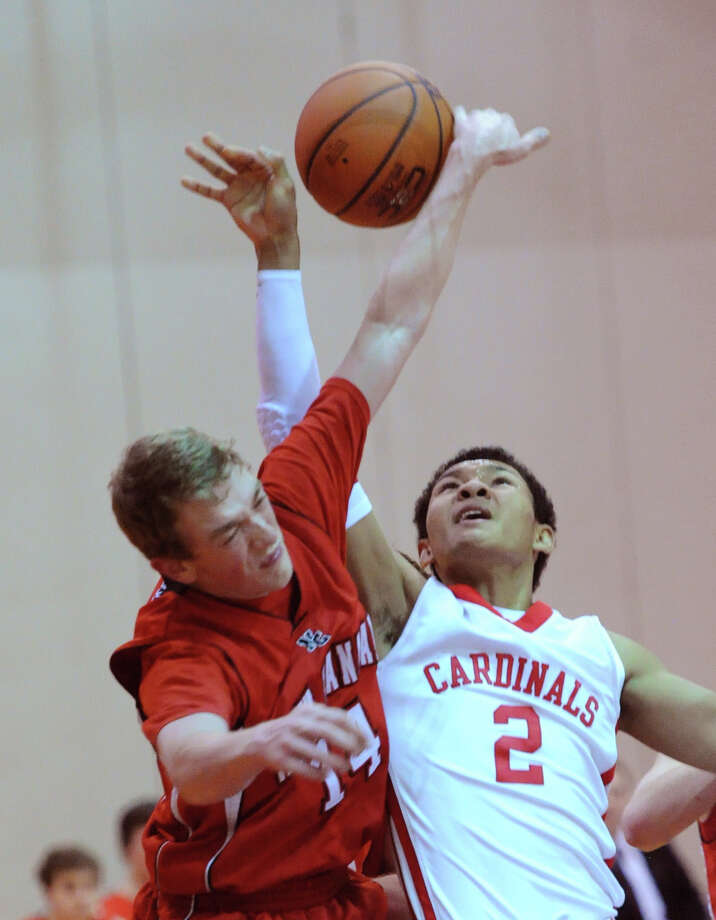 At left, Carsten Berger (# 14) blocks the shot of C. J. Byrd (# 2) of Greenwich during the boys varsity basketball game between Greenwich High School and New Canaan High School at Greenwich, Wednesday night, Dec. 18, 2013. Photo: Bob Luckey / Greenwich Time