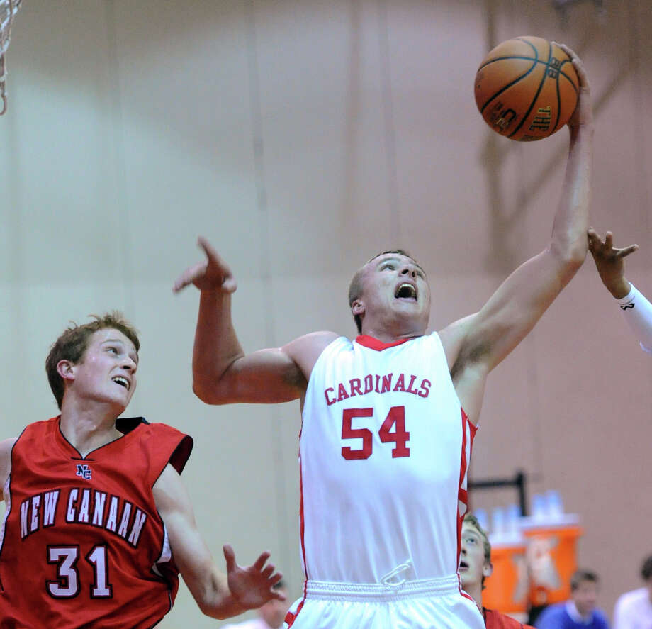 At right, Alex Wolf (# 54) of Greenwich grabs a rebound over New Canaan's Andrew Penchuk (# 31), left, during the boys varsity basketball game between Greenwich High School and New Canaan High School at Greenwich, Wednesday night, Dec. 18, 2013. Photo: Bob Luckey / Greenwich Time