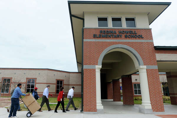Board members of the Beaumont Public School Foundation, Inc., walk into Regina-Howell Elementary School with a pair of WormWatcher tanks in tow Thursday morning. Foundation board members traveled to schools around Beaumont on Thursday morning to hand out grant materials won by six staff members and one student. Instead of monetary prizes, the Foundation supplied the winners with the materials requested. Photo taken Jake Daniels/@JakeD_in_SETX