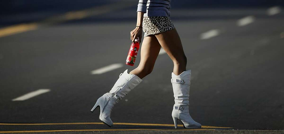 A young woman walks across International Boulevard in Oakland, an area refered to as
