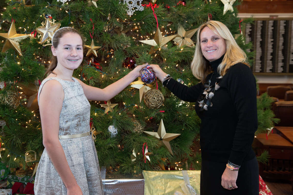 Brianna and Janet Huberty hang an ornament designed by Carsen Hartung on the Texas House of Representatives Christmas tree.