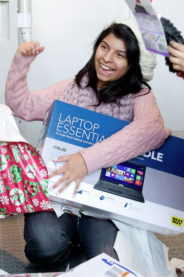 Natalia Ordonez, 16, reacts to her gift of a laptop at Toyota of Stamford on Thursday, December 19, 2013. The gifts, which were for Natalia as well as her mother, Jacqueline Silva, and sister, Sarahi Ordonez, 3, were given to the family to replace some of the things they lost in a major house fire. The money for the gifts was raised at the marathon relay at Stamford Toyota. Gifts included toys for Sarahi, a laptop for Natalia, and gift cards for furniture for the family. Photo: Lindsay Perry / Stamford Advocate