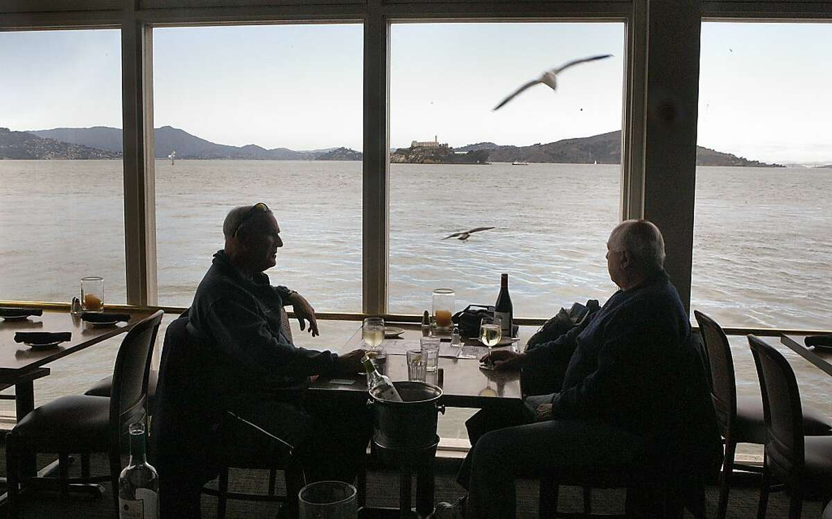 Sailors Dan Abrams (left), from Alameda, and Paul Landsom (right) from Vallejo catch up while wine tasting and enjoying the view at Neptune's Waterfront Grill in San Francisco, Calif., on Tuesday, December 3, 2013.