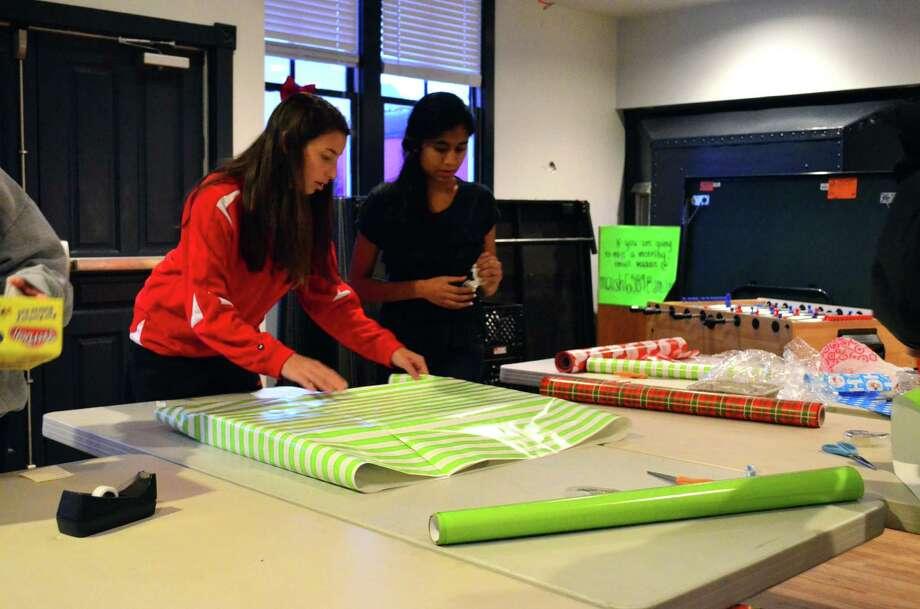 Laura Schartzman, at left, and Sarishka Desai wrap presents at the Darien Depot as part of the annual Holiday Wrap-Up. Photo: Megan Spicer / Darien News