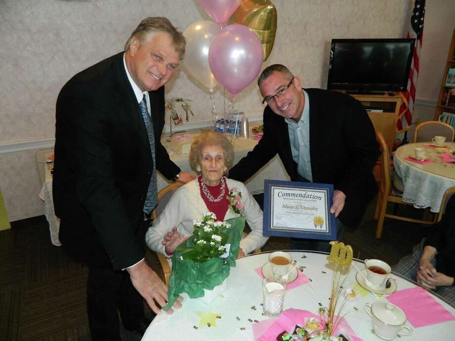 Mary Ormsby marks her 100th birthday on Saturday, Dec. 14, during a party at the Rouse complex in Brunswick. She ran a salon on Troy?s Broadway and now lives in Poestenkill. Rensselaer County Legislator Leon Fiacco and Legislator-elect Rob Bayly presented her with flowers and a proclamation. (Submitted by Rich Crist)