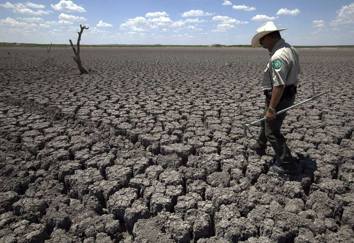 Texas State Park police officer Thomas Bigham walks across the cracked lakebed of O.C. Fisher Lake in San Angelo.