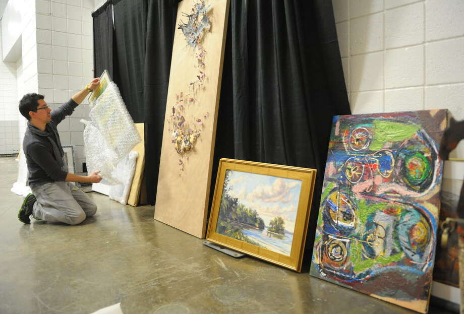 Tony Iadicicco, executive director of Albany Center Gallery, unwraps artwork at the 33rd annual Great Northeast Home Show at the Times Union Center on Feb. 6, 2013 in Albany. The gallery exhibited local artists' work at the home show for the first time last year. (Times Union archive)