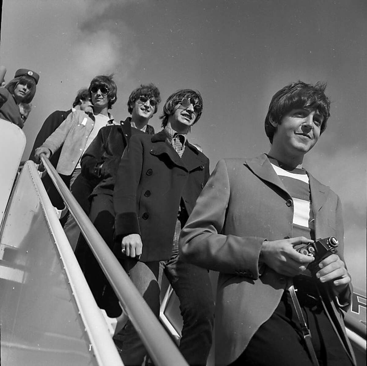 BEATLES6-29AUG1966-BC The Beatles arrive in San Francisco on August 29, 1966 for their concert at Candlestick Park. Paul McCartney, Ringo Starr, John Lennon and George Harrison are shown walking down the stairs from an airplane. CENTURY BOOK
