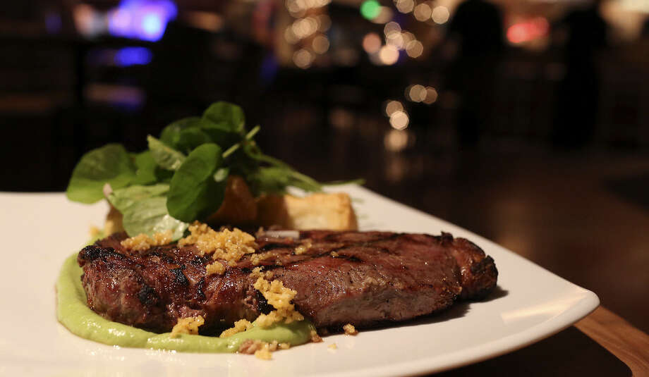 Smoke-roasted rib-eye: A steak that can stand among the tops in the city. An avocado sauce, watercress salad and yuca fries round out the dish. Photo: Photos By Lisa Krantz / San Antonio Express-News / San Antonio Express-News