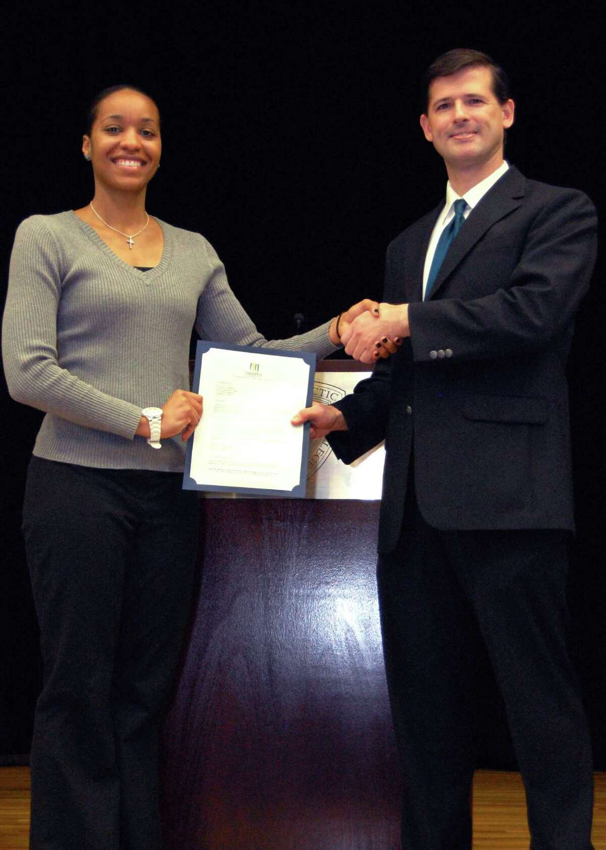 Texas Chiropractic College student Kelley Humphries holds her scholarship certificate with faculty member John Ward.