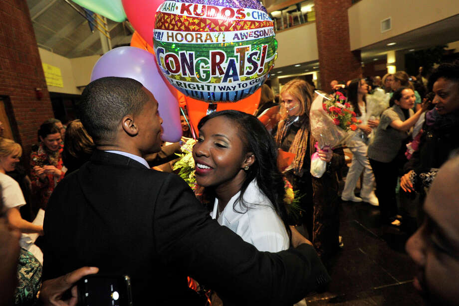 Gerald Ulysse hugs his friend, nursing graduate Joana Lauture, of Stamford, following the Pinning Ceremony for Norwalk Community College nursing students at the college in Norwalk, Conn., on Thursday, Dec. 19, 2013. Photo: Jason Rearick / Stamford Advocate