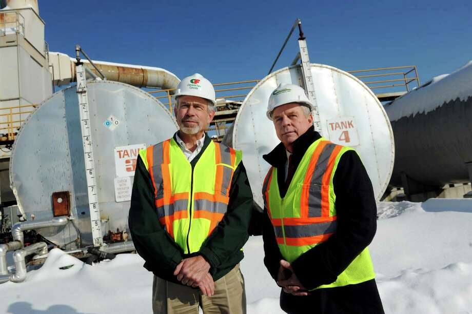 Out-going president Jonas Havens, left, and new company president Don Fane stand by the liquid asphalt tanks on Thursday, Dec. 19, 2013, at Callanan Industries in Schenectady, N.Y. Callan Industries, which makes asphalt that's used in many important projects, is 130 years old. (Cindy Schultz / Times Union) Photo: Cindy Schultz / 10025099A