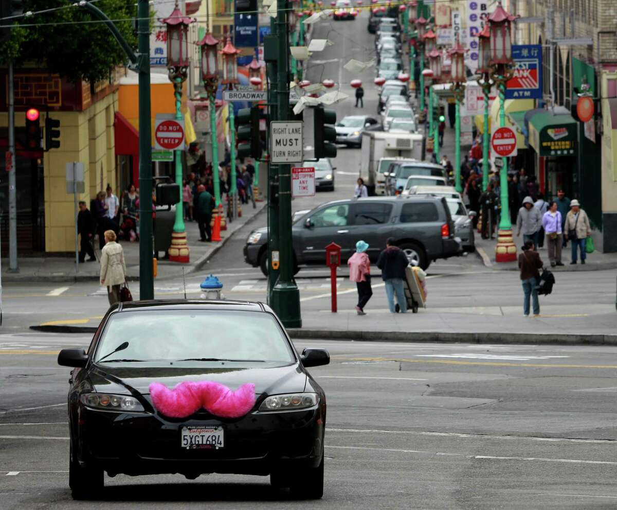 Cars driven by Lyft passenger service workers in the North Beach neighborhood of San Francisco sport a large pink mustache.