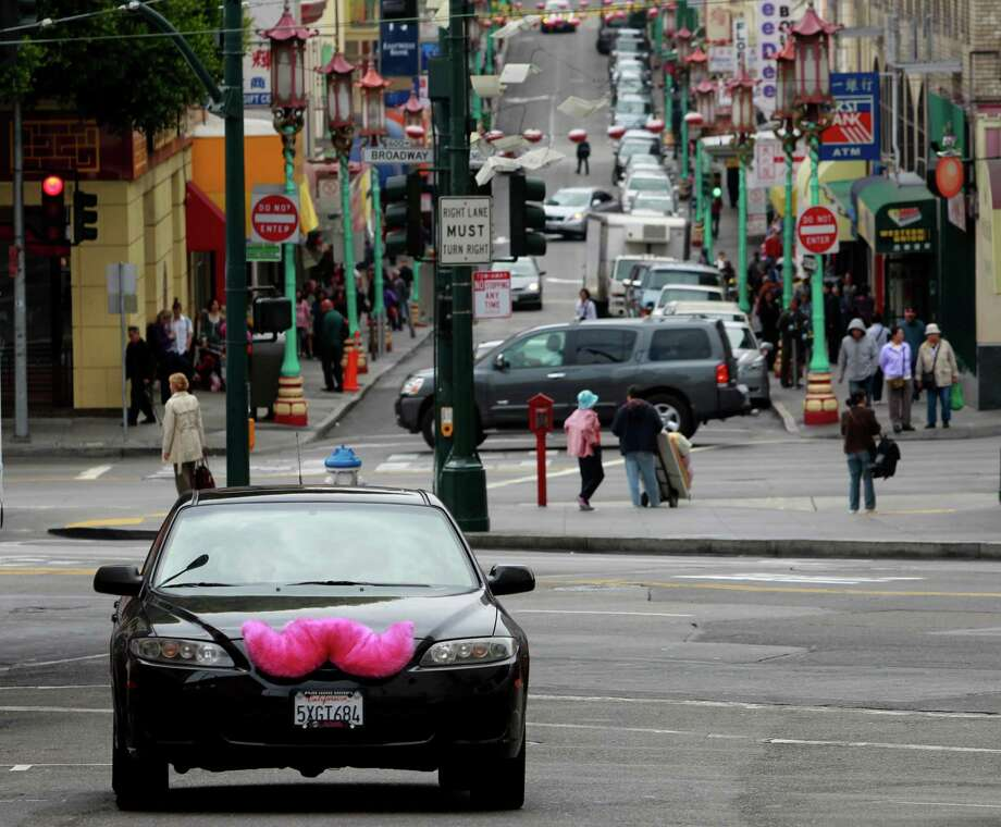 Cars driven by Lyft passenger service workers in the North Beach neighborhood of San Francisco sport a large pink mustache. Photo: Paul Chinn, Staff / ONLINE_YES