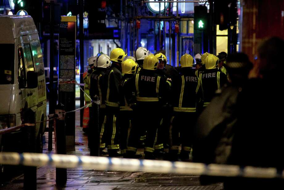 """Firemen confer at the scene following an incident at the Apollo Theatre, in London's Shaftesbury Avenue, Thursday evening, Dec. 19, 2013, during a performance at the height of the Christmas season, with police saying there were """"a number"""" of casualties. It wasn't immediately clear if the roof, ceiling or balcony had collapsed  during a performance. Police said they """"are aware of a number of casualties,"""" but had no further details. (AP Photo by Joel Ryan, Invision) Photo: Joel Ryan, INVL / INVISION"""