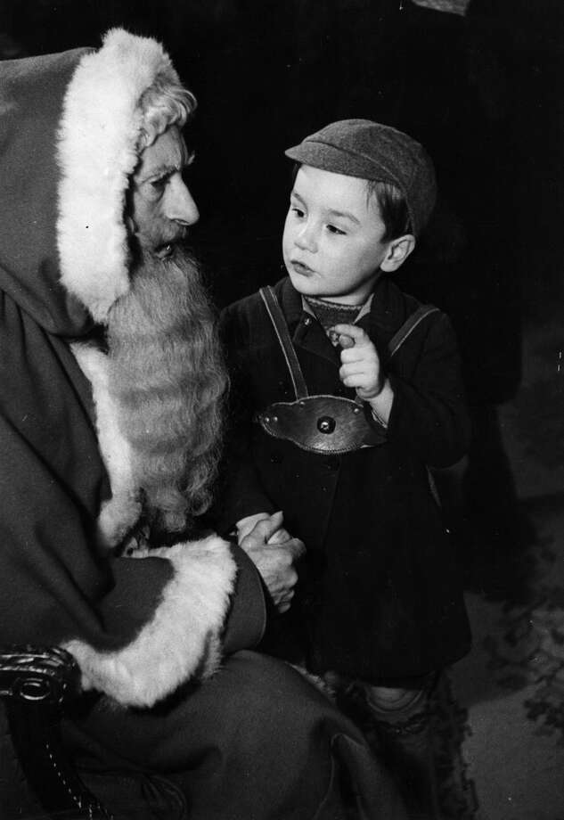 This little boy at John Barkers store in London seems fascinated by Father Christmas' beard on Dec. 18, 1948. Photo: Kurt Hutton, Getty Images / Picture Post