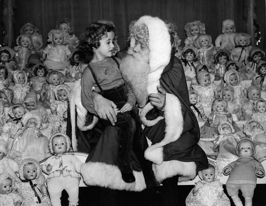 A vast number of dolls surrounds Father Christmas as he talks to a girl sitting on his knee on Nov. 13, 1937. Photo: Fox Photos, Getty Images / Hulton Archive
