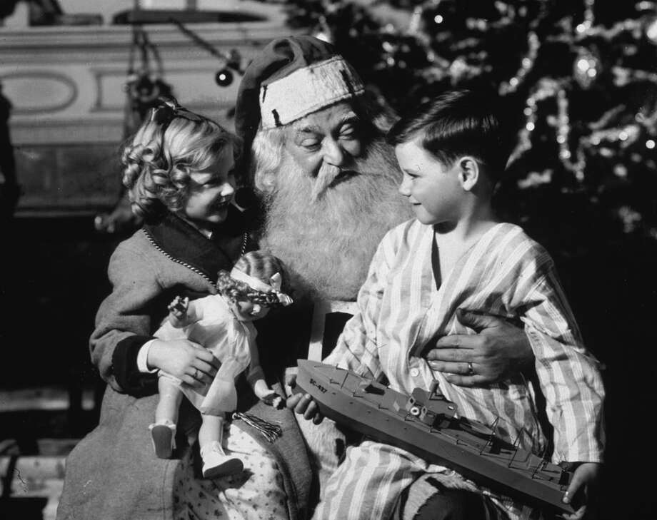 A small boy and girl sit on Santa Claus's lap in front of a Christmas tree, circa 1935. The girl holds a doll and the boy holds a model of a battleship. Photo: Camerique Archive, Getty Images / Archive Photos