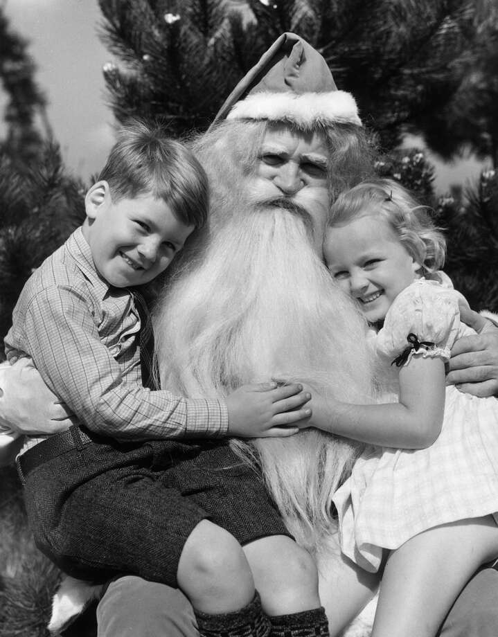 A young girl and boy hug Santa Claus while sitting on his lap, circa 1945. Photo: Lambert, Getty Images / Archive Photos