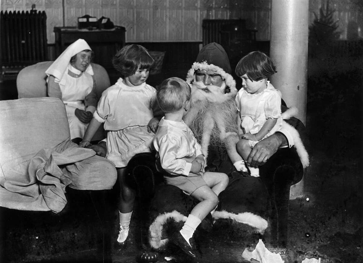 Santa Claus tells a story to a group of children at the Stadium Club in the United Kingdom in December 1922.