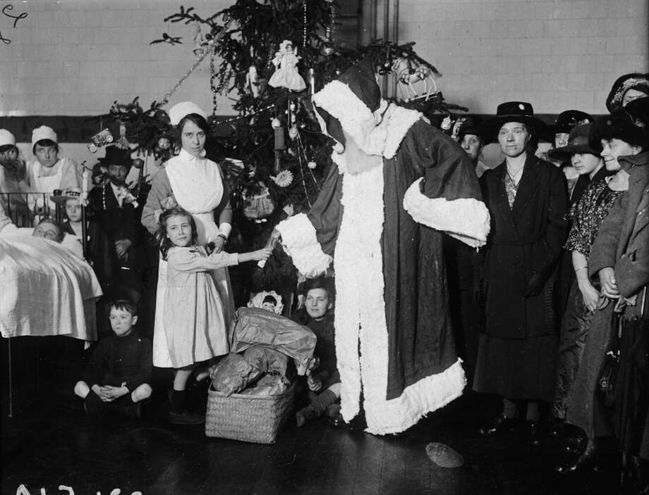 Santa helps children celebrate at a Christmas party at Queens Hospital in the United Kingdom, circa  1925. Photo: Topical Press Agency, Getty Images / Hulton Archive