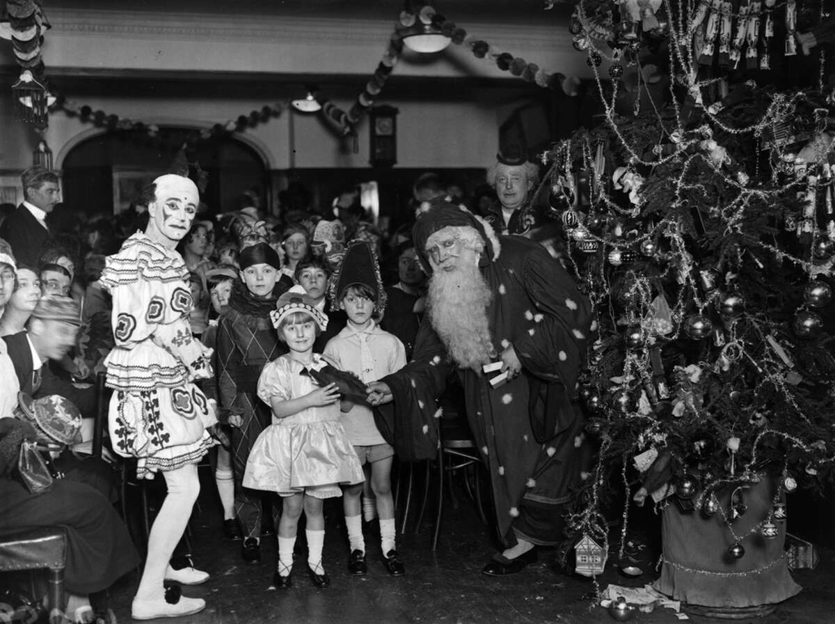 Father Christmas gives out presents at a children's party given by journalists at the Press Club in December 1924.