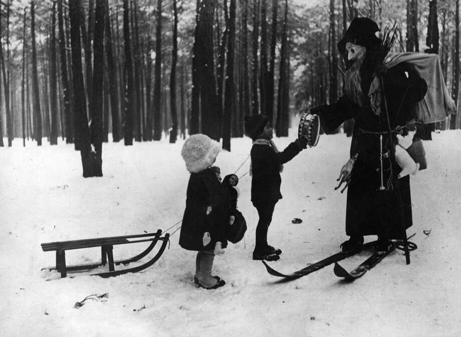 A Swiss Santa Claus, on skis, has a present for a little boy, circa 1930. Photo: Hulton Archive, Getty Images / Hulton Archive