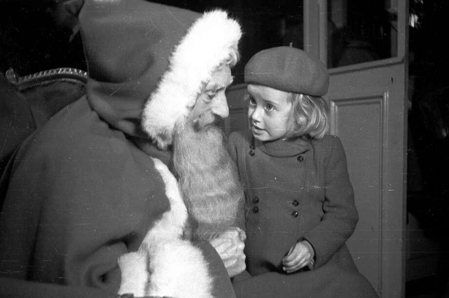 A little girl tells Santa Claus what she would like for Christmas at John Barkers store in London on Dec. 18, 1948. Photo: Kurt Hutton, Getty Images / Picture Post