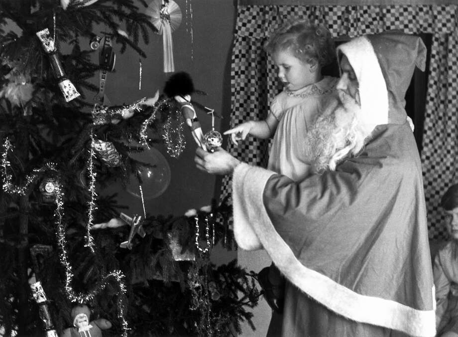 Father Christmas and a young child admire the decorations on a Christmas tree in 1930. Photo: Science & Society Picture Library, Getty Images / SSPL/NMeM/Kodak Collection